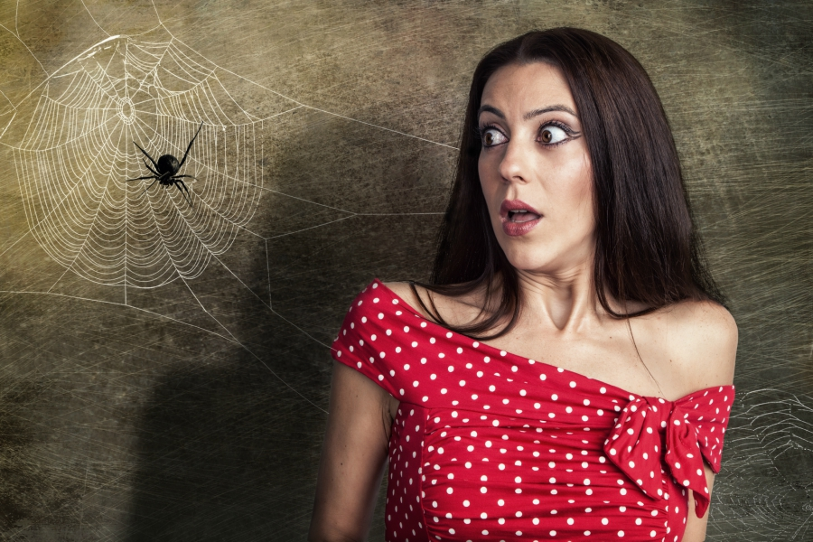 Girl in red and white polka dot top scared by a spider