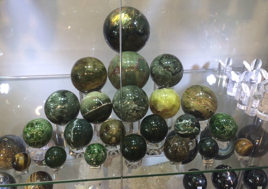 A group of spherical green crystals sitting on a clear shelf