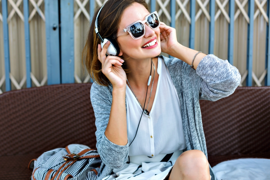 Girl wearing a white blouse and a gray cardigan with sunglasses and headphones on listening to music