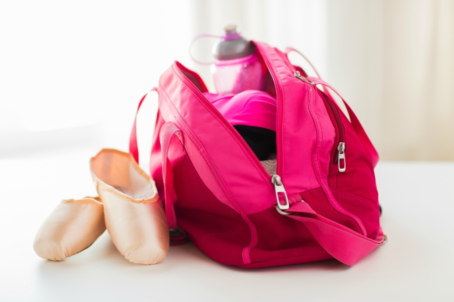 Pink dance bag with pointe shoes and water bottle.