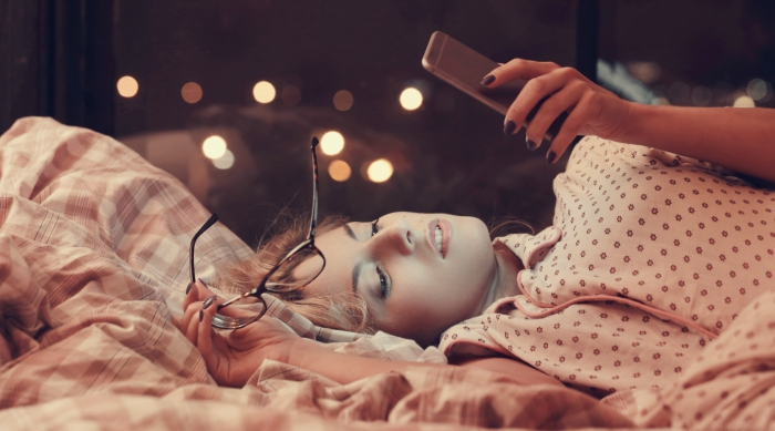 Girl scrolling through her phone on bed at night.