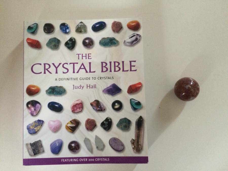 The Crystal Bible by Judy Hall book and an Ocean Jasper crystal