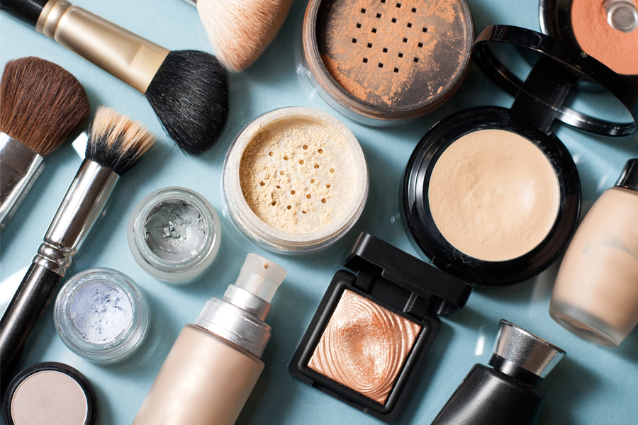 Beauty products on blue background with makeup brushes