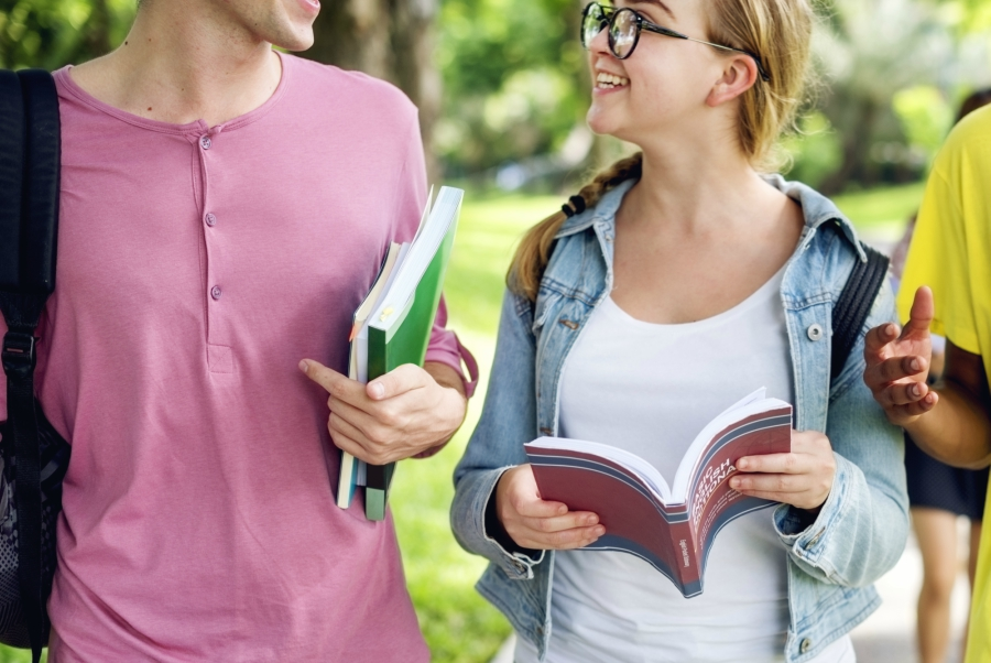 Girl and guy walking and talking about a book