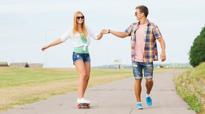 Teen girl and boy skateboarding