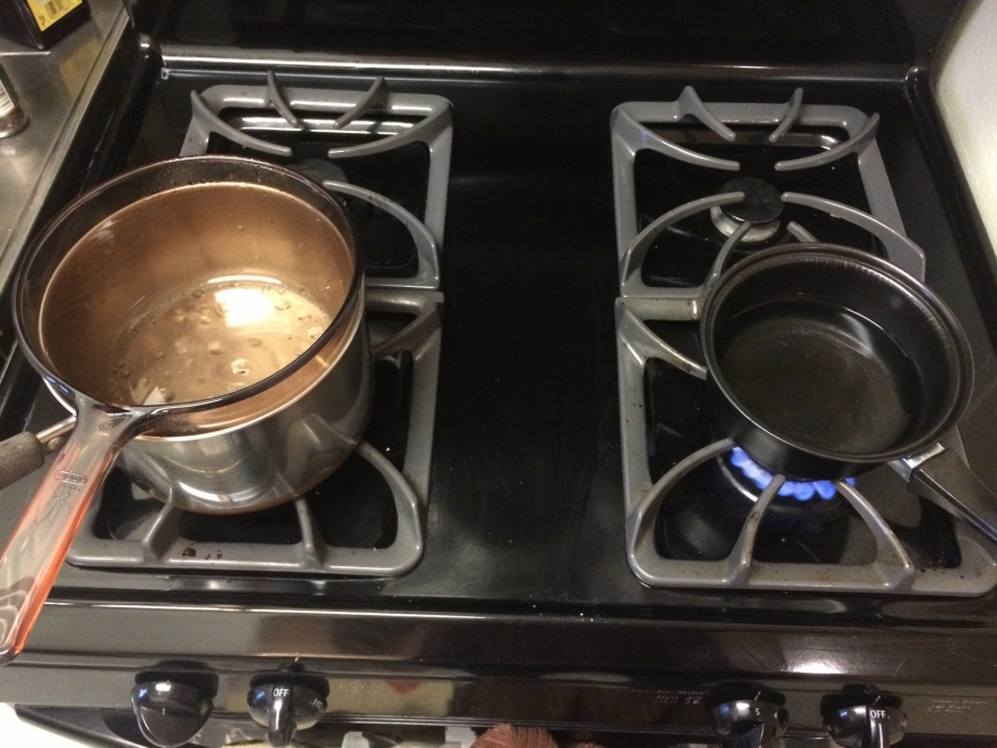 Pans on a stovetop over an open flame