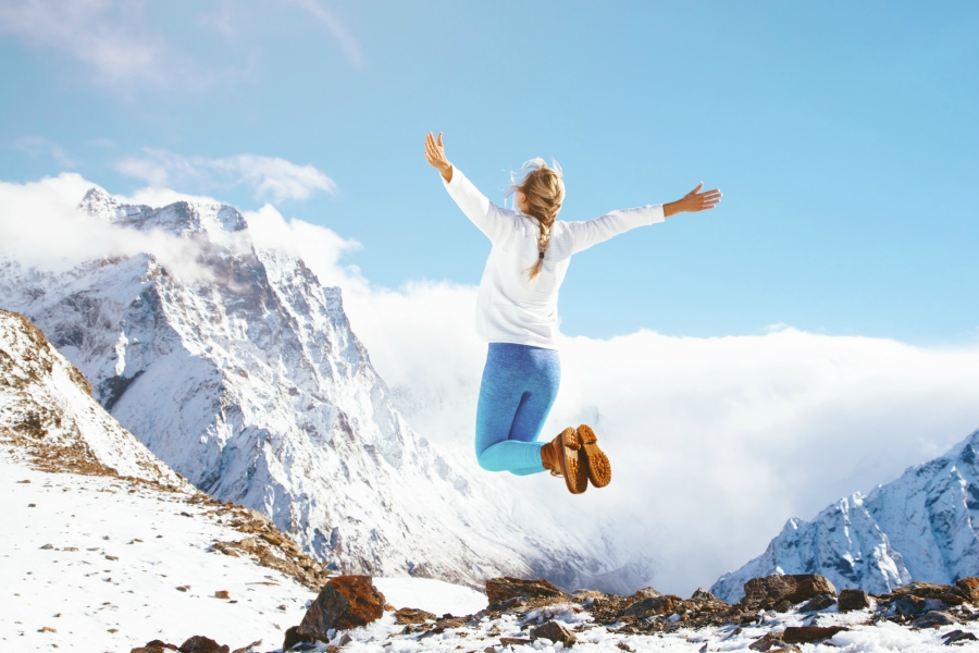 Girl jumping in snowy mountains
