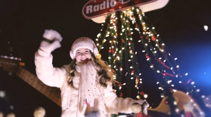 "Tegan Marie singing ""Just Another Night"" during a holiday parade on a Radio Disney float"