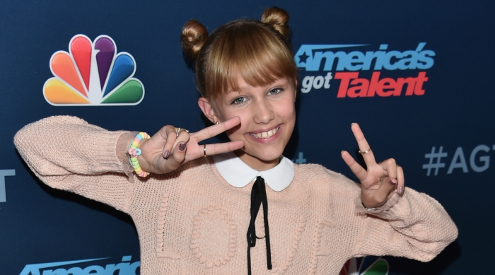 Grace VanderWaal at America's Got Talent throwing up the peace sign on both hands