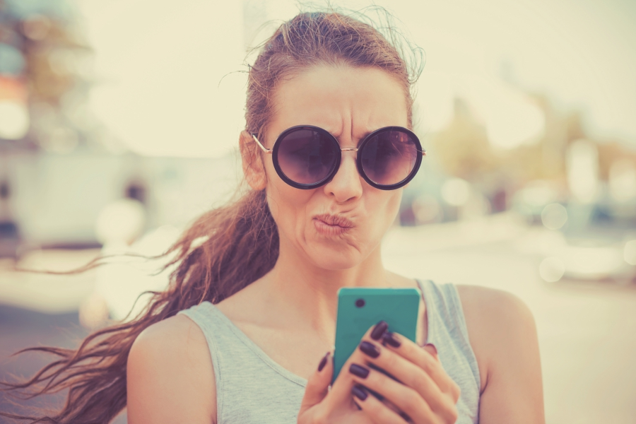 Girl looking at cell phone quizzically