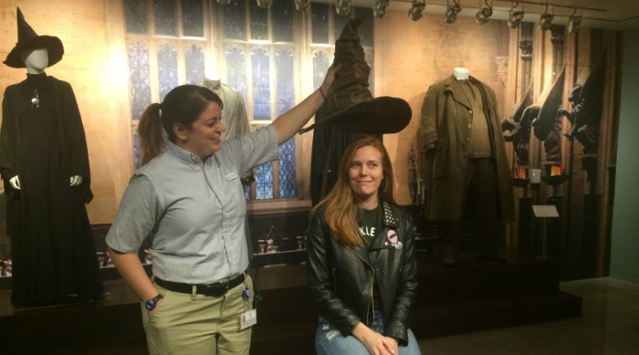 Blonde girl being sorted into a Hogwarts house with the sorting hat at the warner bros. studio tour