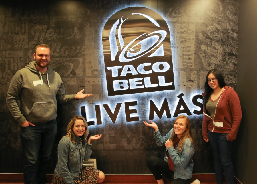 Sweety High staff in front of Taco Bell Liv Mas sign