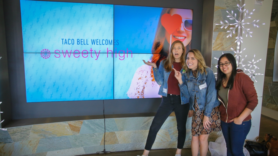 Sweety High staff in front of welcome sign at Taco Bell headquarters