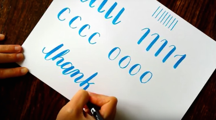 Girl writing in calligraphy style using blue marker