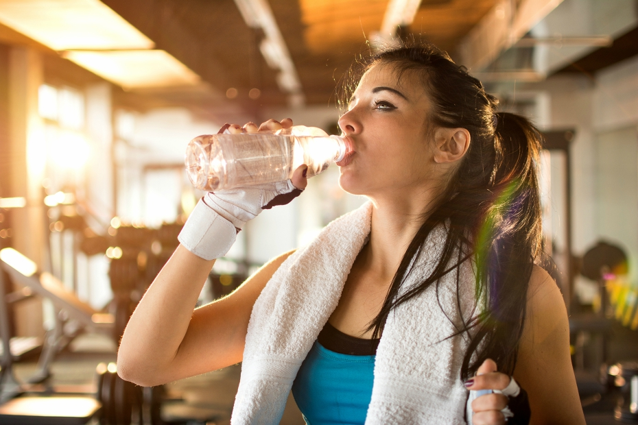 girl at gym chugs water