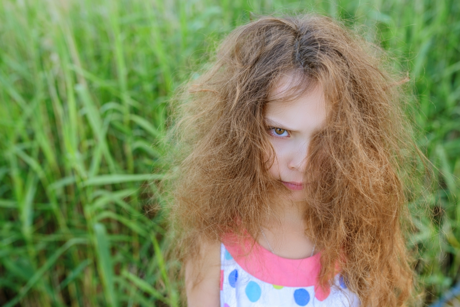 A very unhappy girl has frizzy hair