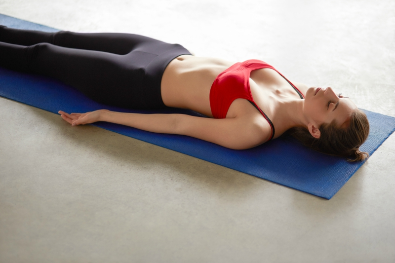 Female in a red sports bra and black yoga pants laying down while meditating on a blue yoga mat