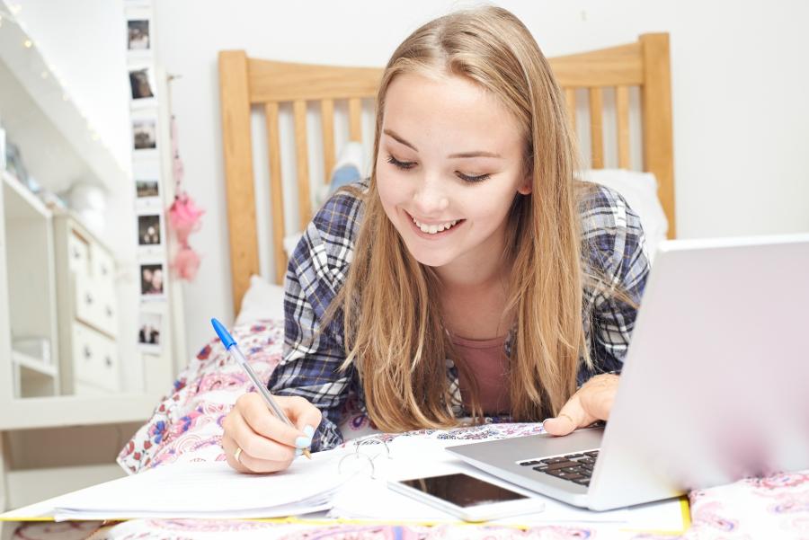 Teenage girl doing homework on her bed