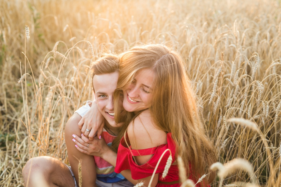 A teenage girl and guy hugging in a field