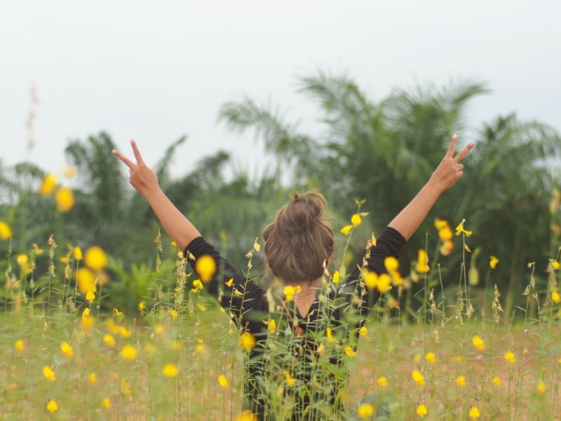 Girl in a field of flowers holding up peace sign