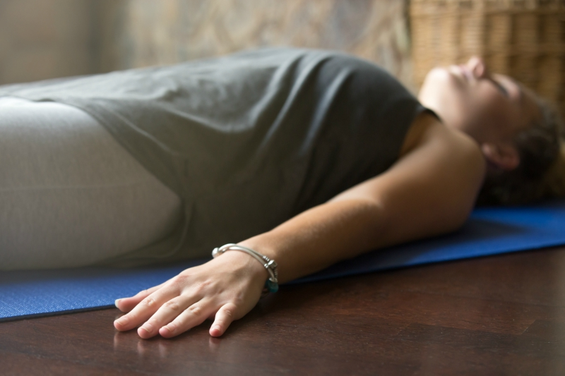 Girl laying on her back on a yoga mat