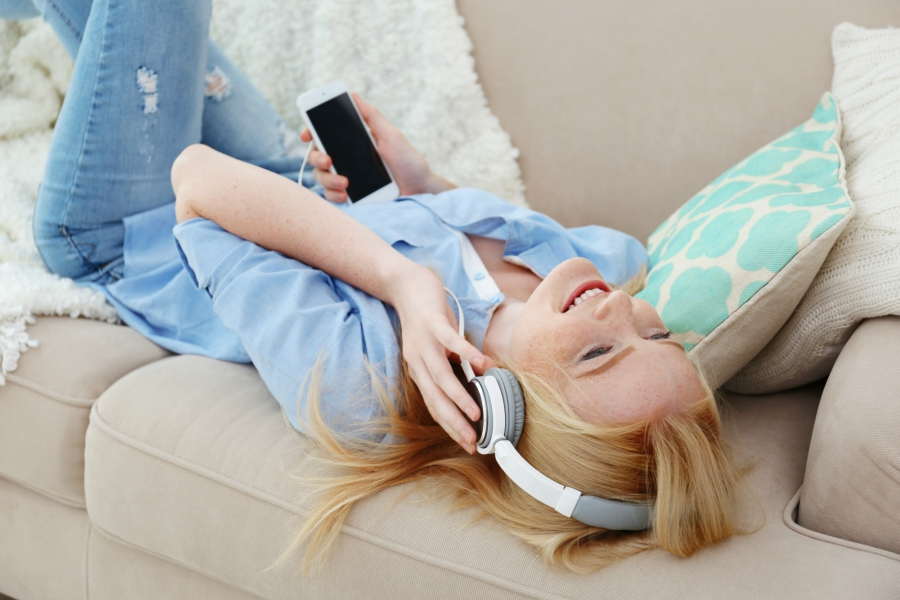 Girl listening to music on her bed