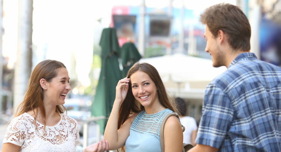 Two girls and a guy flirting
