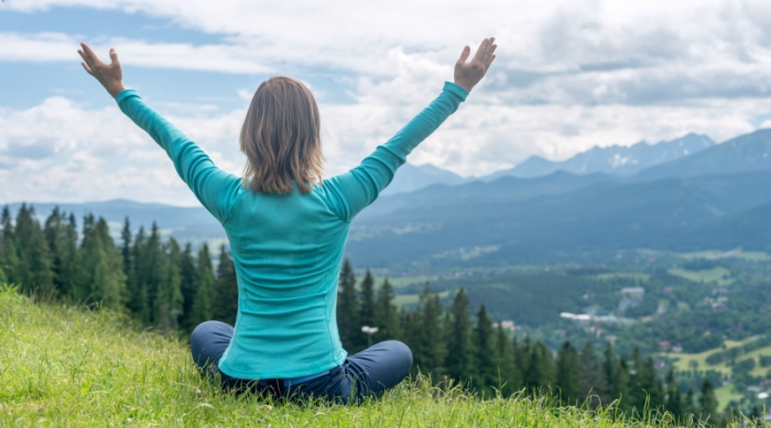 Girl meditating on mountain top with her arms stretched above her head