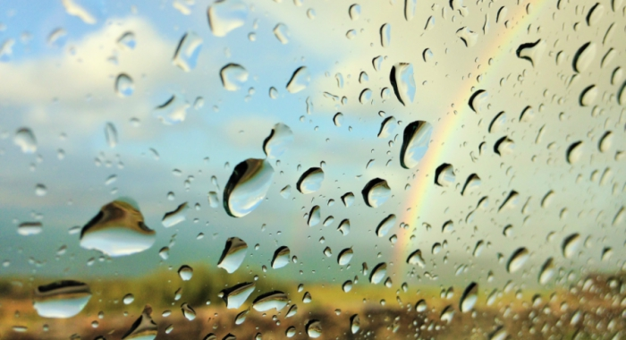 artsy shot of the rain on a window with rainbow in background