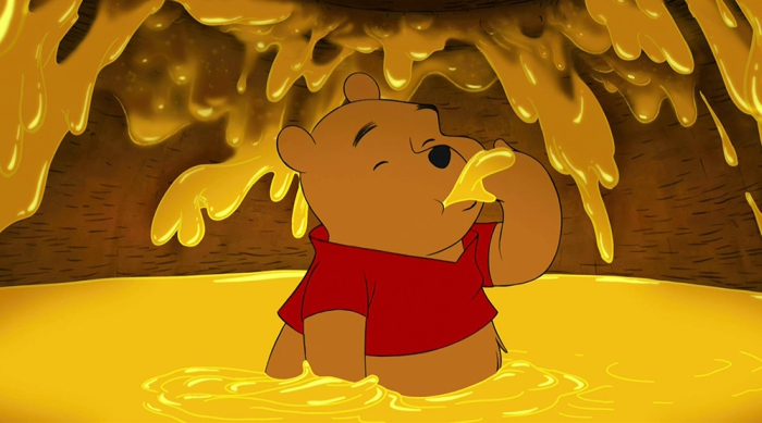 Pooh sitting in a tub of honey