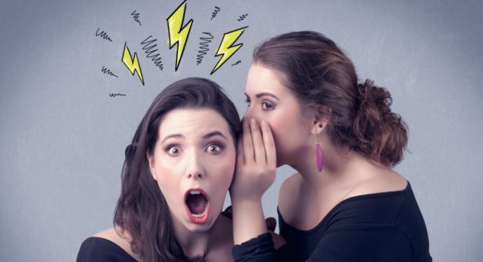 Two girls telling a secret