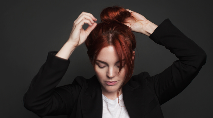 Red head Allison McNamara putting her hair in a bun with bangs