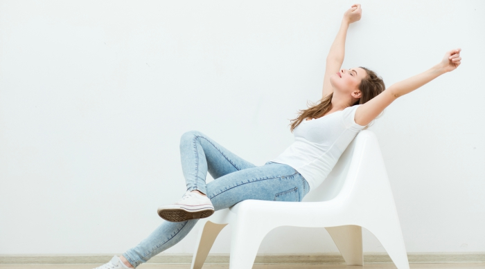 Girl in a tee and jeans sitting in a white chair and stretching her arms to the ceiling