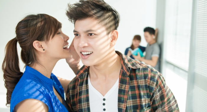 A girl whispers in a guy's ear