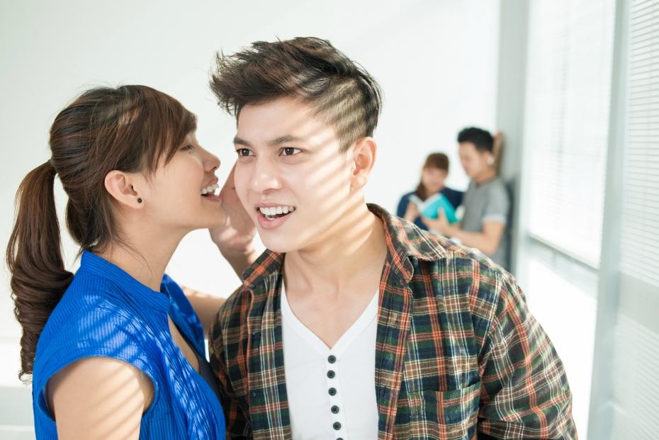 A girl whispers a secret in a guy's ear