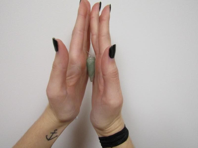 Girl holding turquoise pendulum between her hands