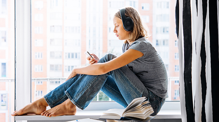 Girl listening to music through headphones while sitting on a windowsill