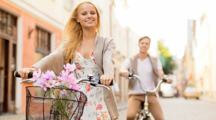 Blonde girl riding a bike with flowers in the front basket, while her male date is in the background
