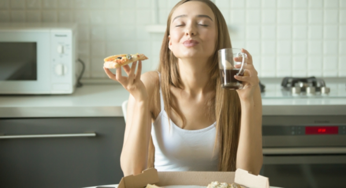girl is so happy eating pizza and drinking coffee