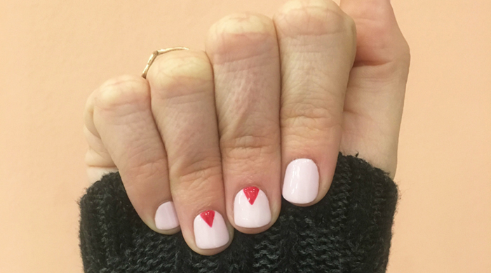 A pink and red manicure on a pink backdrop