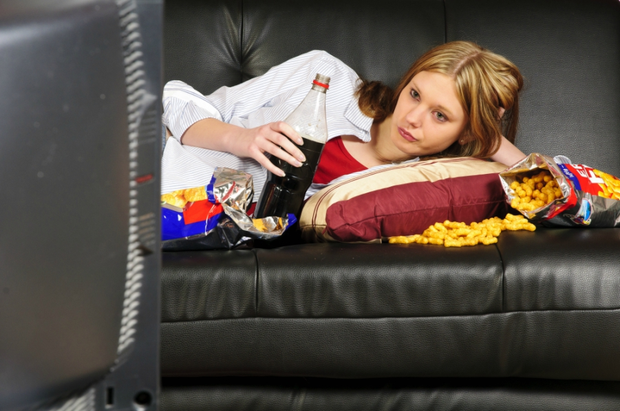 Girl watching TV while eating a ton of junk food on the couch