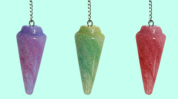 A purple, green and red pendulum on a teal background