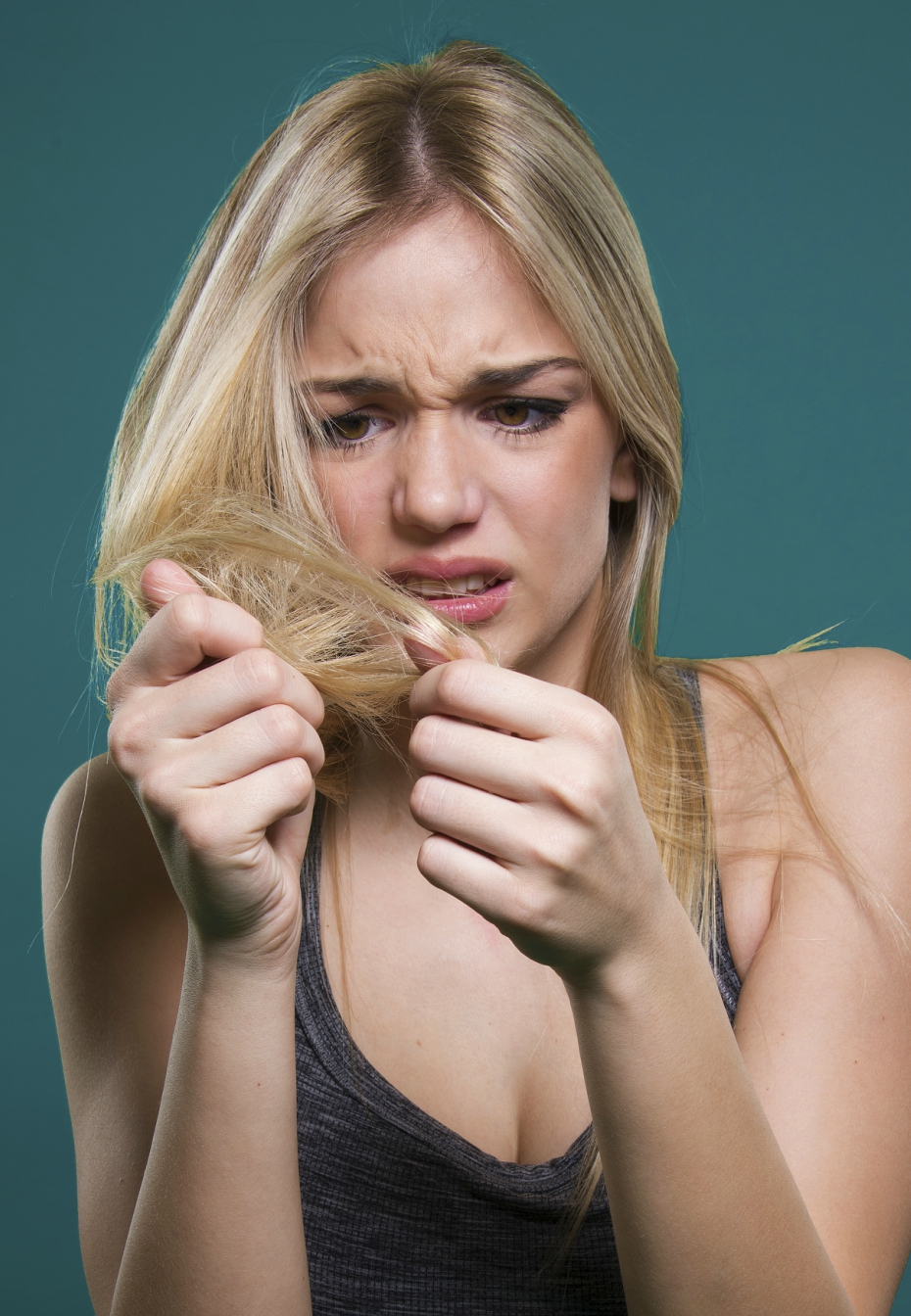 blonde girl seems frustrated while looking at hair