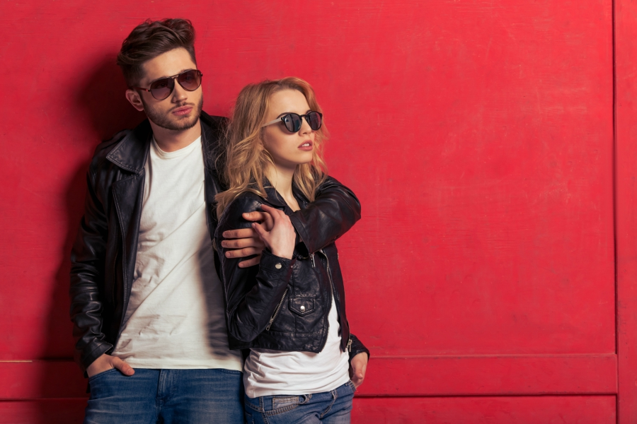 Female and male couple in matching leather jackets standing in front of a red wall