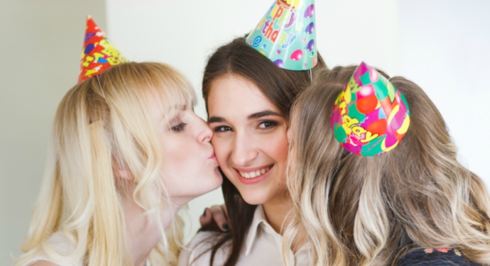 A girl receives a kiss from two friends on her birthday