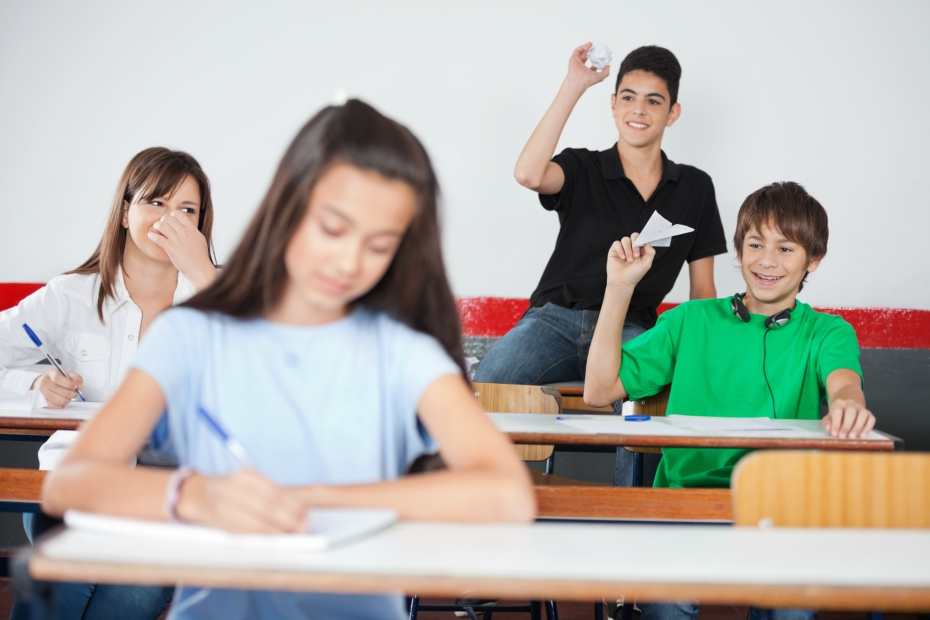 rowdy kids throw paper airplanes in the middle of class