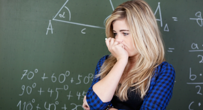 upset girl stands in front of chalkboard in math class