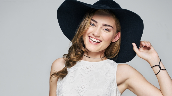 American Housewife actress Meg Donnelly smiling at camera while wearing a black wide-brimmed hat