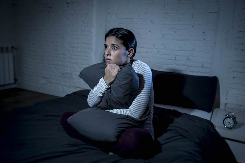 girl clutches pillow in bed after bad nightmare