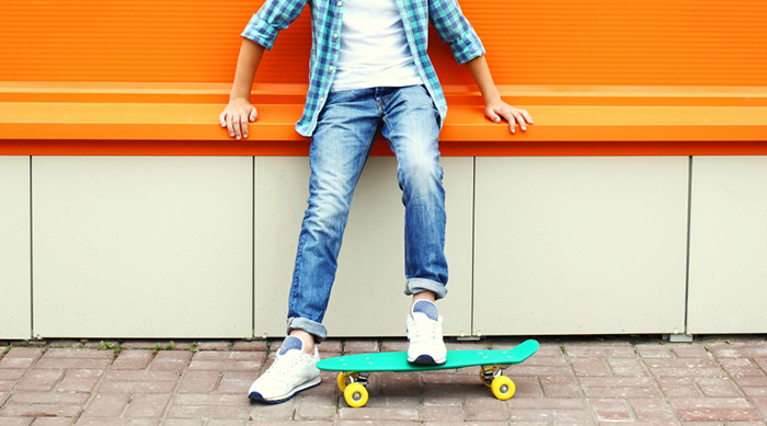 A boy on a skateboard in front of an orange wall